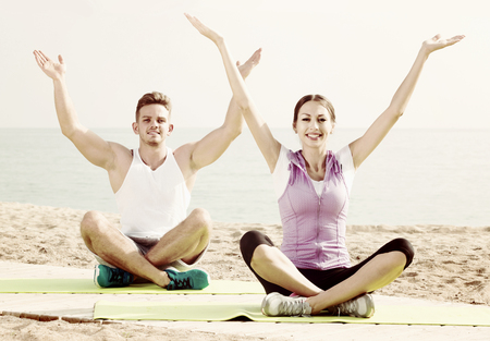 Cross-legged european positive couple practice yoga on beach in morning