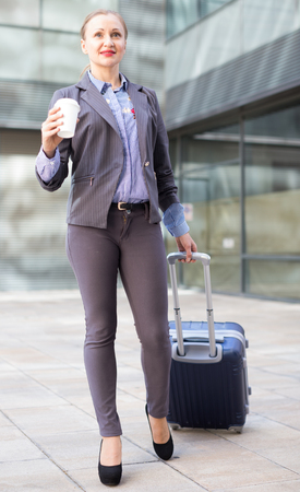 Smiling woman worker going with baggage and keeping coffee in the hand