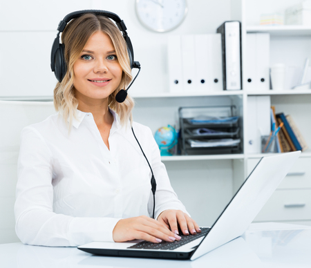 Young call center employee in headphones is sitting near laptop in the office