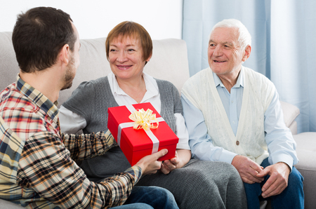 Son gives gift in red box to his elderly parents for holiday Banque d'images