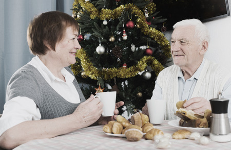 Smiling elderly couple having breakfast at festive Christmas table Stock Photo