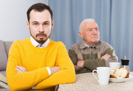 Aged father teaches and instructs his young son at table at home Stock Photo