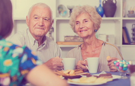 Happy senior couple enjoying conversation with female guest over cup of coffee at home