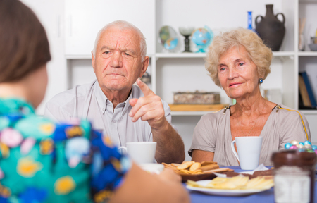 Upset elderly pair sitting at table, having tough talk with young girl