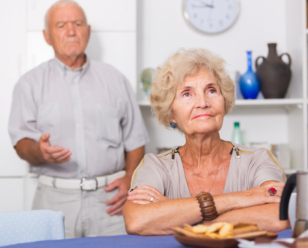 Elderly upset woman sitting separately having problems in relationship with husband  Stock Photo