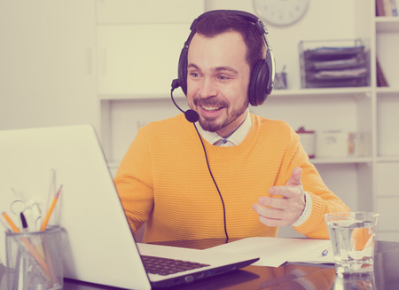 Young man runs distance learning and pleased solving problems in office