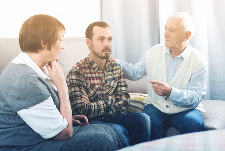 Elderly grandfather talking seriously with his grandson in presence of grandmother