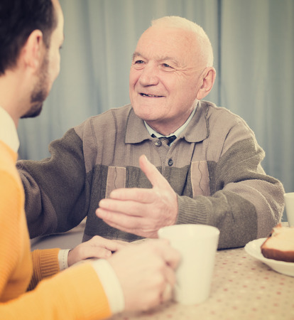 Aged father and his son drinking coffee and talking at table at home