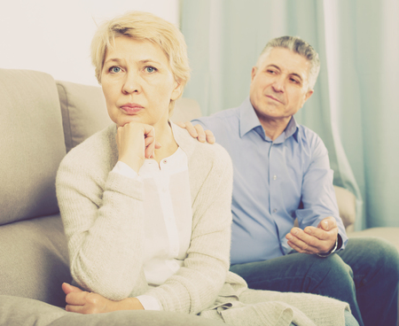 upset middle-aged couple quarreling at home with each other and take offense Stock Photo