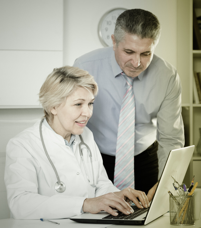 Mature doctor and manager discussing news information on clinic site