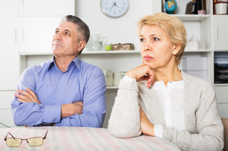 Senior husband and wife quarrels with each other at clarification of the family relation in home Stock Photo