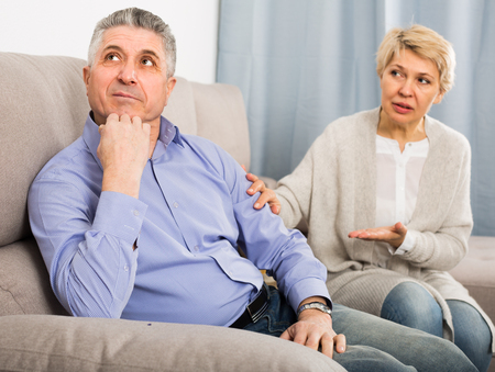 Mature friends are offended at each other because of the misunderstanding in his home. Stock Photo