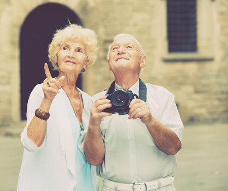 Happy positive smiling mature couple on traveling together, photographing city attractions with camera