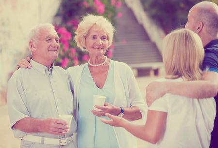 Glimlachende oudere mensen die en bij plastic kop bij openlucht spreken drinken
