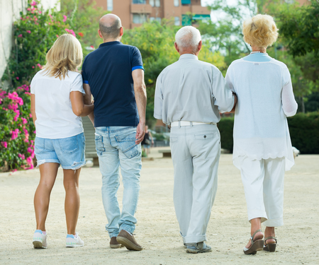 Positive group of four mature people walking in the garden