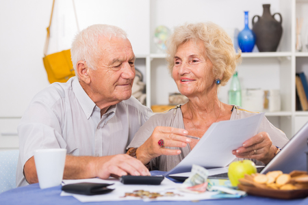 Smiling senior couple sitting at table counting home finances with laptop