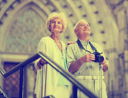 Portrait of mature couple of tourists standing with suitcases and camera in front of cathedral