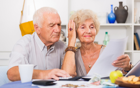 Worried mature man and woman having financial problems and analyzing bills