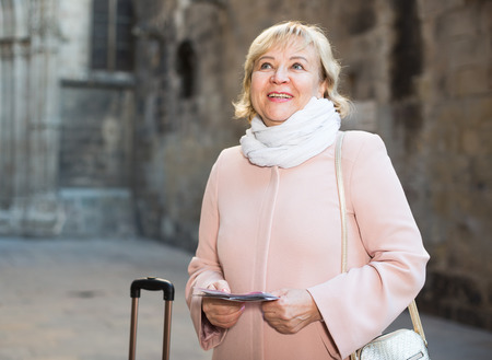Mature woman with map and baggage in the old city autumn season