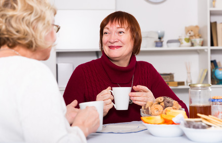 Smiling pensioners females talking at home with cup of tea