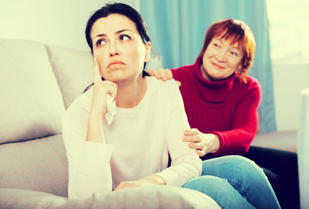 Unhappy women sitting at sofa after conflict at home interior together