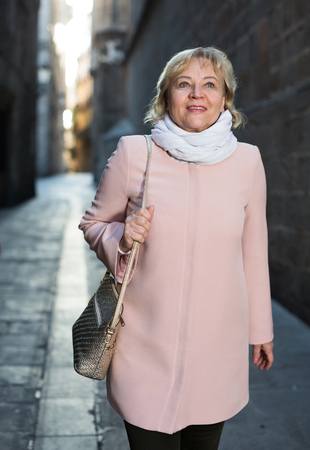portrait of mature female in the historical city center in scarf Stock Photo