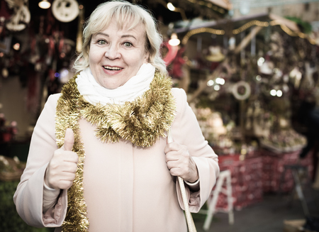 Positive female in tinsel on Christmas fair decoration on holiday Stock Photo