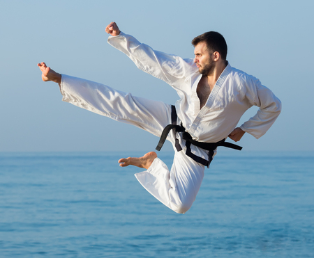 Young man shows his skills in karate on the sea beach