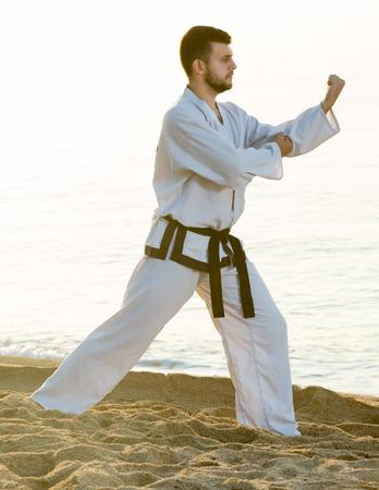 Young   man practising karate poses at seaside in sunset outdoor
