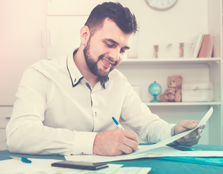 Smiling happy young man signing profitable financial agreement at home 写真素材