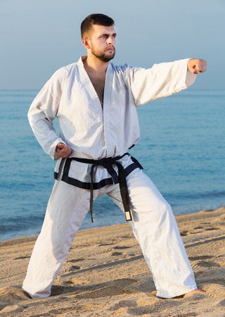 Adult happy man doing karate at ocean quay in dawn