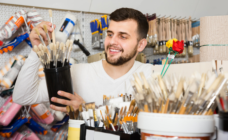 friendly male customer examining various types of brushes in paint supplies store Фото со стока