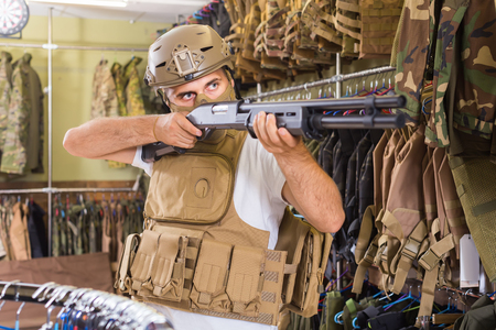 Young guy in military equipment with gun in airsoft shop  Stock Photo