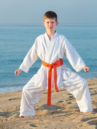 Handsome boy doing karate at ocean quay Stock Photo