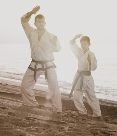 Man and boy in karate uniform training at sunny sea beach