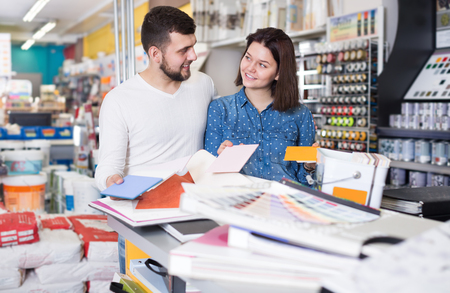 Smiling couple examining a various decorative materials in paint supplies store. Focus on both persons