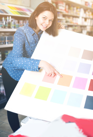 Young female is deciding on best color scheme in paint supplies store. Stock Photo
