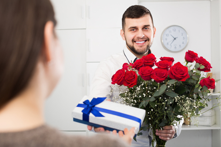 Positive young guy presented bouquet and gift for romantic dinner