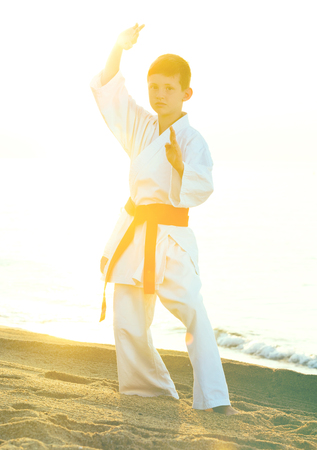 Young boy practicing karate positions at ocean quay