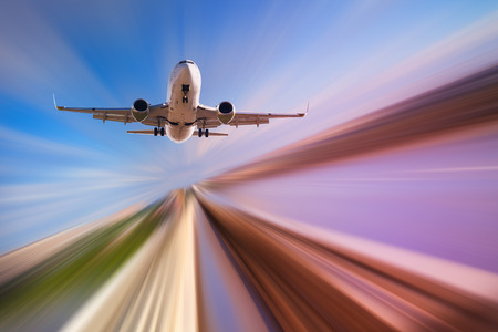 Airplane in motion over roadway on blur blue sky background