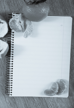 Notebook with empty pages lying amid decoration of tangerines
