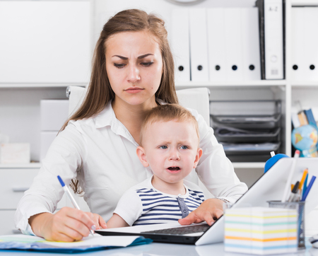 Serious girl with child is сoncentratedly working behind laptop in office.