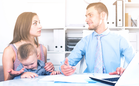 Portrait of manager of insurance company talking with female with child Stock Photo
