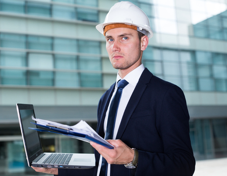 Builder in suit and hat with folder is looking into documents with project and comparing in laptop near the building. Stock Photo