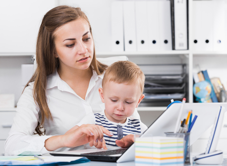 Woman with child is working behind laptop in office.