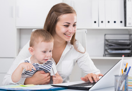 Satisfied mother with kid is productively working behind laptop in office.