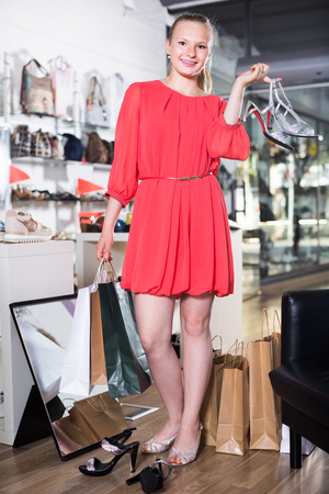 Cheerful girl posing in new sandals in heels in a shoe store