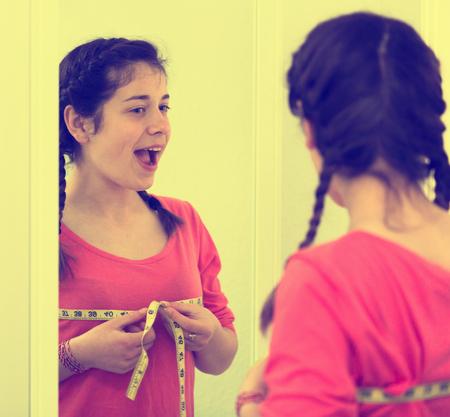 Jong meisje dat succesvol met de thuiswinst van de borstgrootte voelt