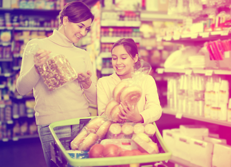 Cheerful female shopper with teenage daughter searching for bread in supermarket Stock Photo