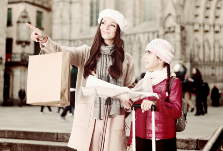 adult female and daughter in the city center in scarf with map Imagens